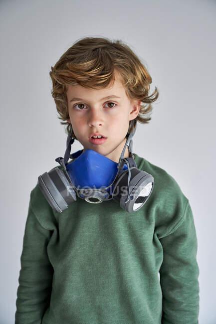 Блондин, около 8 лет, носит респиратор, чтобы заразить себя вирусом. — стоковое фото
