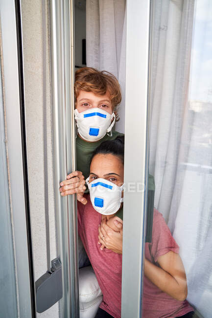 Mother and child looking out their home window to see if the danger of possible infection has passed — Stock Photo
