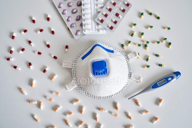 Masque respiratoire avec gel antibactérien et pilules avec un thermomètre sur la table de chambre — Photo de stock