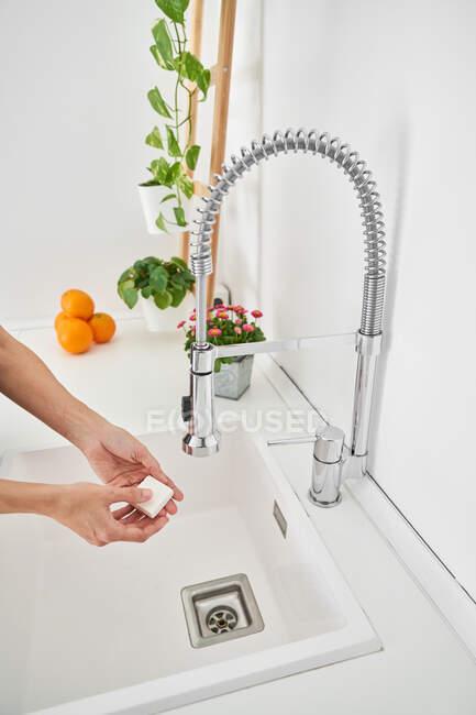 Женщина моет руки на кухонной раковине, чтобы избежать возможной инфекции — стоковое фото