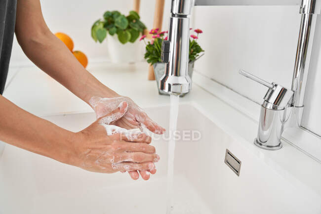 Woman washing her hands on the kitchen sink to avoid possible infection — Stock Photo