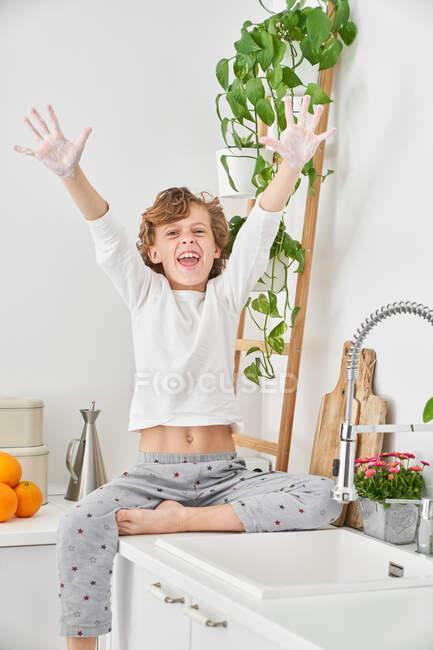 Criança loira lavando as mãos na pia da cozinha para evitar qualquer infecção — Fotografia de Stock