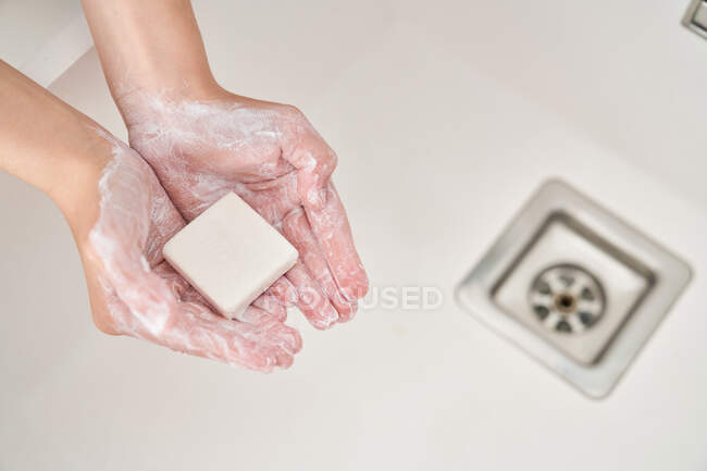 Cropped image of child washing his hands in the kitchen sink to prevent any infection — Stock Photo