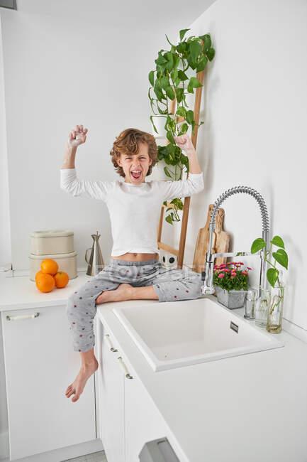 Niño rubio lavándose las manos en el fregadero de la cocina para prevenir cualquier infección - foto de stock