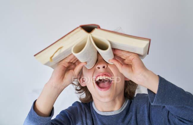 Blond garçon en pyjama en utilisant un livre comme jumelles — Photo de stock