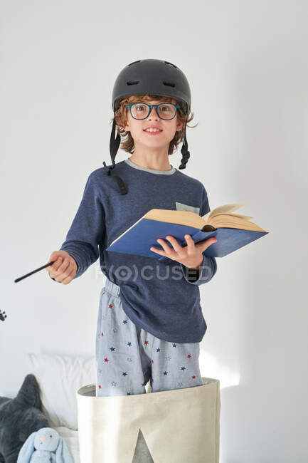 Blond kid in pajamas with a helmet and a book playing research — Stock Photo
