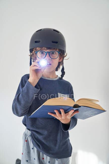 Блондинка в піжамі з шоломом і книга, що грає в дослідження — стокове фото