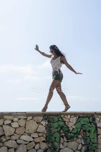 Повнометражний портрет безтурботної бронетки жінки в шортах танцює на стіні проти моря — стокове фото