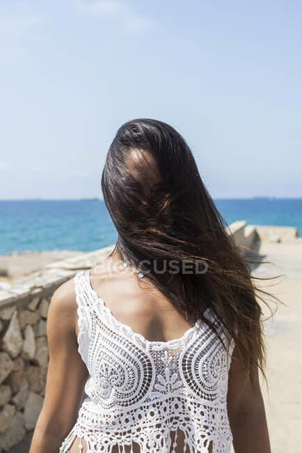 Donna ispanica dai capelli lunghi copre il viso da lunghi capelli dal vento all'aperto — Foto stock