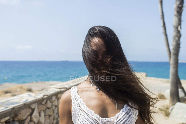 Long haired hispanic woman covers the face by long hairs by wind outdoors — Stock Photo