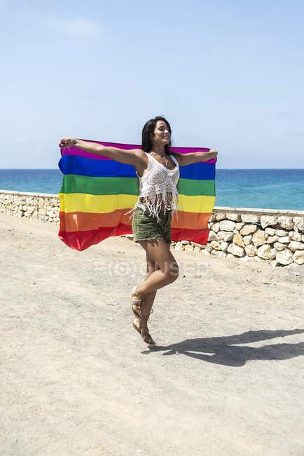 Портрет латиноамериканки, играющей с флагом lgtb — стоковое фото