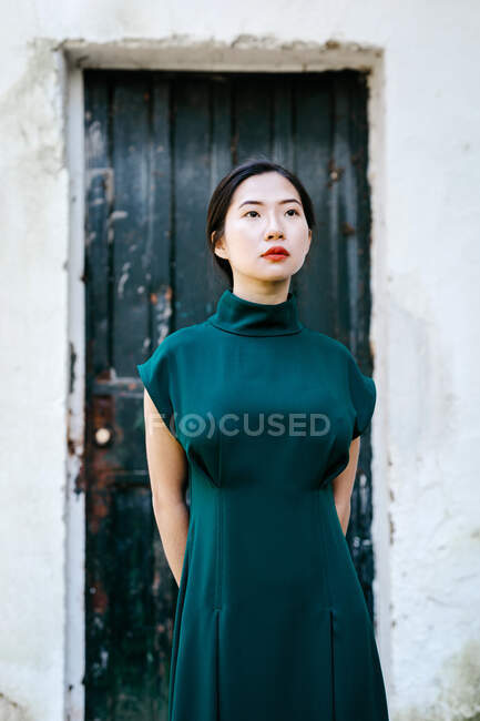 Young asian woman in trendy dress keeping hands behind back and looking up while standing against aged building with shabby door — Stock Photo