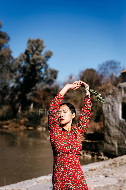 Stylish asian woman with closed eyes holding thin branch in raised arms while standing near peaceful lake on cloudless day in countryside — Stock Photo