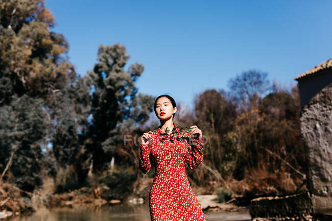 Stylish asian woman with closed eyes holding thin branch while standing near peaceful lake on cloudless day in countryside — Stock Photo