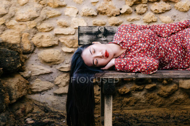 Asiatin in trendiger floraler Kleidung auf alter Holzbank liegend mit geschlossenen Augen gegen Steinmauer — Stockfoto