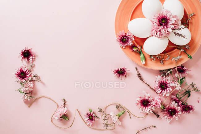 Зверху видніються витончені квіти, розміщені біля тарілки з яйцями курки на рожевому фоні. — стокове фото