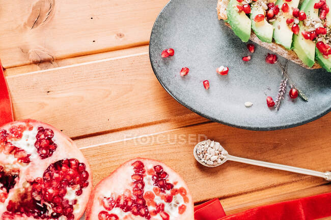 Top view of halved pomegranate and spoon with seeds placed near plate with delicious avocado toast on wooden table — Stock Photo
