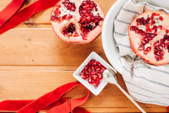 Top view of red ribbon placed on lumber table near plate with halves of ripe pomegranate and spoon — стокове фото