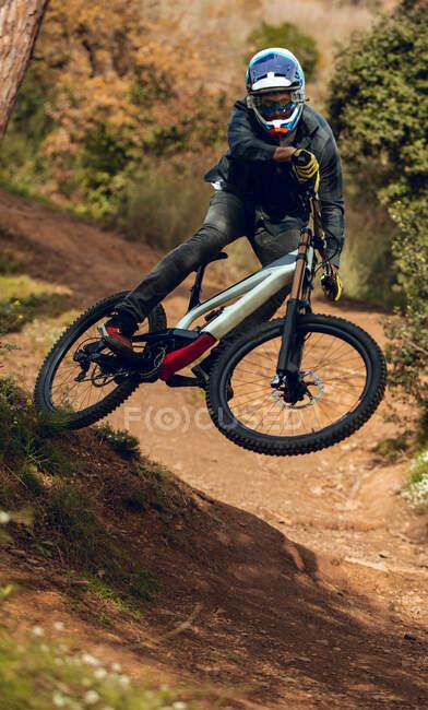 Неузнаваемый человек в шлеме, перчатках и защитных очках, прыгающий вниз по склону во время занятий горным велосипедом в лесу — стоковое фото