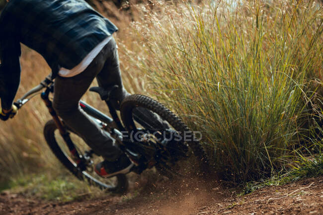Back view of cropped unrecognizable man in helmet going downhill during mountain biking practice in wood forest — Stock Photo