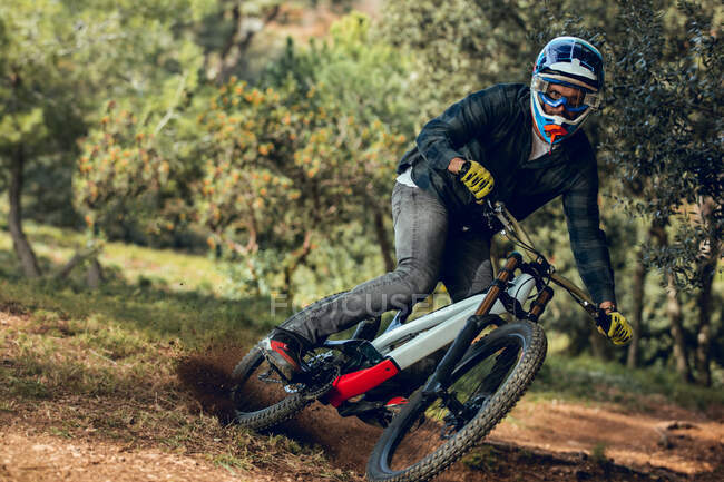 Неузнаваемый человек, смотрящий на камеру в шлеме, перчатках и защитных очках, прыгающий вниз во время тренировки горных велосипедов в лесу — стоковое фото