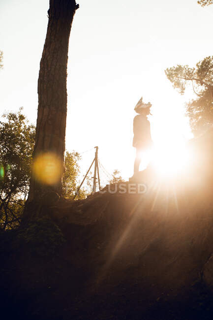 Deportista de ciclismo de montaña irreconocible de pie en la cima de la colina durante la puesta de sol en el bosque - foto de stock
