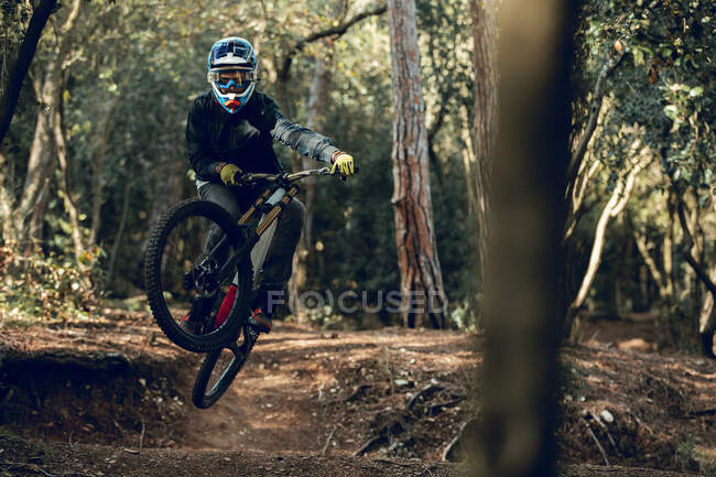 Unrecognizable man in helmet, gloves and protection glasses jumping doing whip trick downhill during mountain biking practice in wood forest — Stock Photo