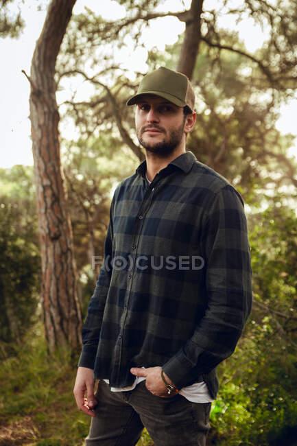 Ritratto di bell'uomo bruno in camicia a scacchi e berretto da baseball in piedi sullo sfondo della natura guardando la macchina fotografica — Foto stock