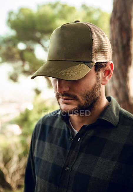 Ritratto irriconoscibile di uomo bruno in camicia a scacchi e berretto da baseball in piedi sullo sfondo della natura guardando in basso — Foto stock