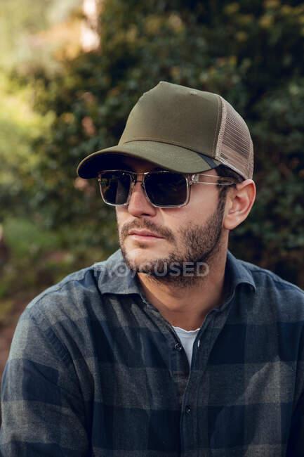 Портрет вродливого чоловіка з мішаною сорочкою і бейсбольною шапочкою, що стоїть на задньому плані природи. — стокове фото