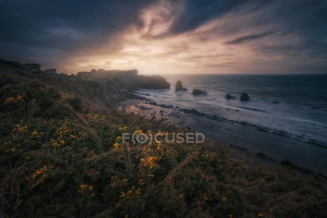 Magnifique paysage de côte rocheuse et vagues de mousse océanique troublées pendant le coucher du soleil — Photo de stock