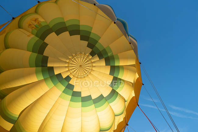 Big vivid yellow and green air balloon against clear blue sky in fair weather — Stock Photo