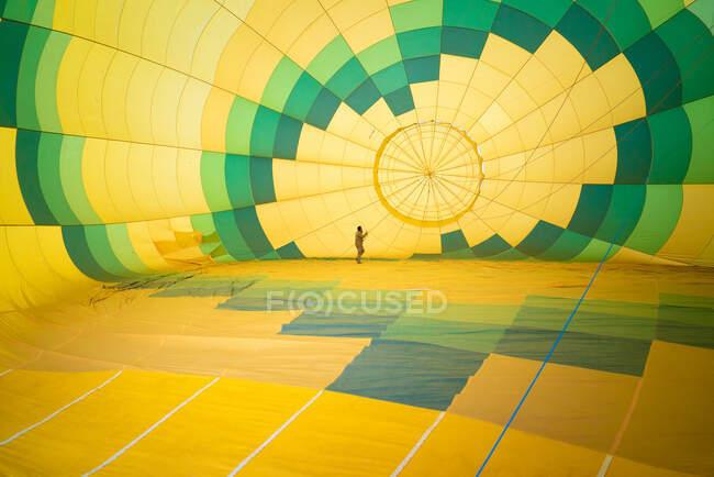 Нерозпізнаваний чоловік перевіряє стан великої зеленої і жовтої повітряної кулі, стоячи всередині і проводячи технічне обслуговування. — стокове фото