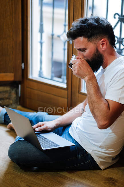 Bearded man sipping hot drink and reading data from laptop while sitting on floor and working on remote project at home — Stock Photo