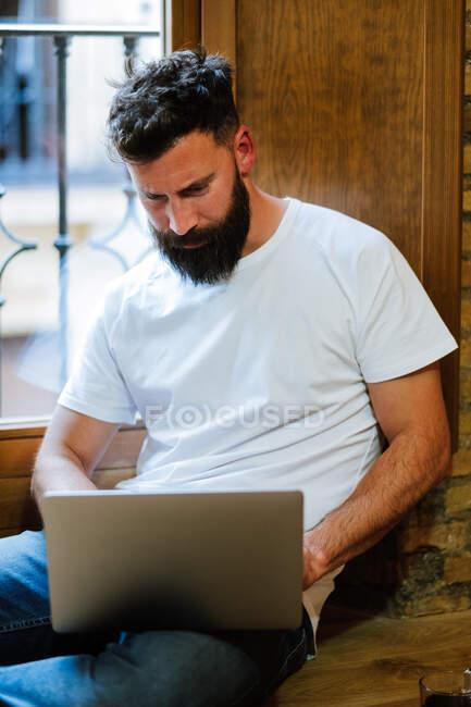 Freelancer barbudo usando laptop en casa - foto de stock