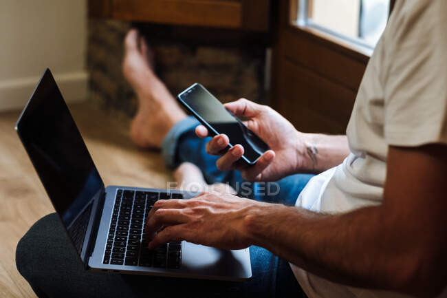 Unrecognizable man sitting on floor and using laptop and smartphone while working on remote project at home — Stock Photo