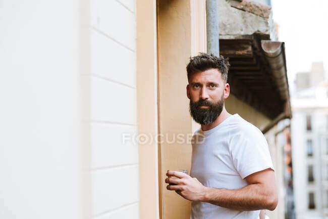 Бородатый парень с горячим напитком отдыхает на балконе — стоковое фото