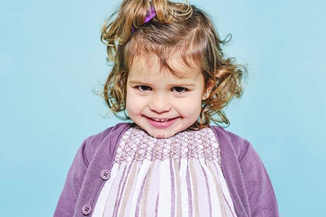Colheita pré-escolar alegre em vestido violeta e cardigan de malha sorrindo para a câmera enquanto em pé contra o fundo azul claro no estúdio — Fotografia de Stock