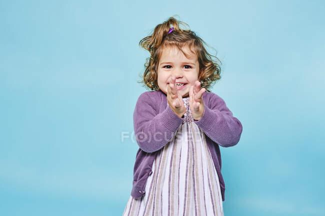 Allegro bambino piccolo in abito viola e cardigan lavorato a maglia sorridente alla fotocamera e battendo le mani mentre in piedi da solo contro lo sfondo azzurro in studio moderno — Foto stock