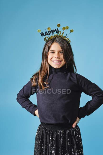 Pré-adolescente feliz em capacete preto e dourado com desejos feliz Ano Novo sorrindo para a câmera com as mãos nos quadris contra fundo azul claro no estúdio moderno — Fotografia de Stock