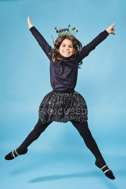 Trendy overjoyed kid in festive headgear and black clothes jumping and smiling at camera while celebrating New Year against light blue background in studio — Stock Photo