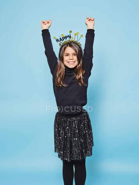 Criança na moda alegre demais em chapéus festivos e roupas pretas levantando os braços sorrindo para a câmera enquanto celebra o Ano Novo contra o fundo azul claro no estúdio — Fotografia de Stock