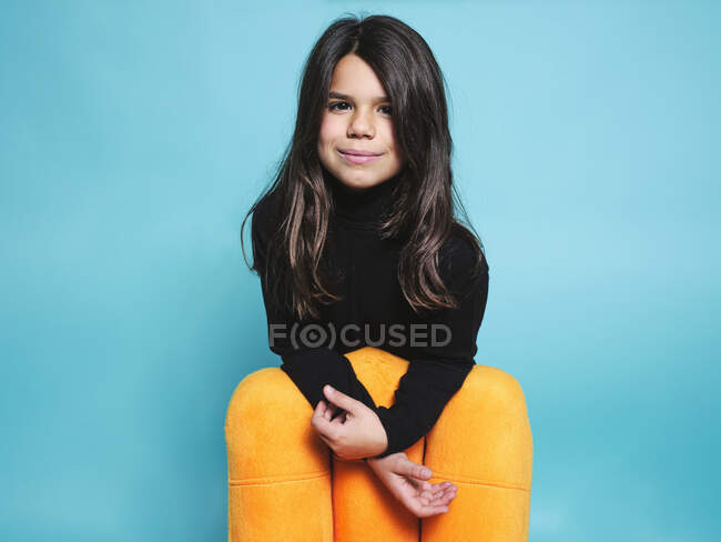 Happy preteen girl in black casual clothes smiling looking at camera while leaning behind yellow armchair against light blue background in contemporary studio — Stock Photo