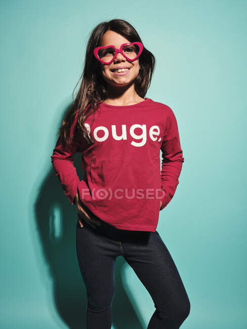 Happy preteen girl in pink heart shape glasses and casual clothes smiling away while standing with hands on hips against turquoise background in modern studio — Stock Photo
