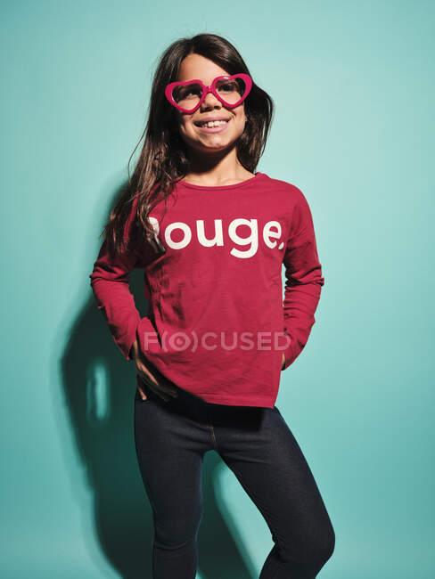 Chica preadolescente feliz en gafas de forma de corazón rosa y ropa casual sonriendo mientras está de pie con las manos en las caderas contra el fondo turquesa en el estudio moderno - foto de stock