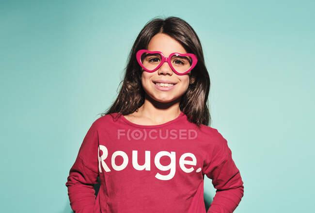 Счастливая девочка-подросток в розовых очках в форме сердца и повседневной одежде, улыбаясь в камеру, стоя на бирюзовом фоне в современной студии — стоковое фото