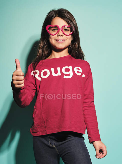 Happy preteen girl in pink heart shape glasses and casual clothes smiling at camera with thumbs up standing against turquoise background in modern studio — Stock Photo