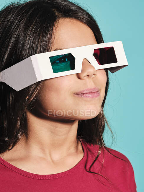 Portrait of happy preteen girl in white plastic stereoscopic glasses with red and blue lens smiling away while watching 3d graphic film with pleasure against turquoise background in modern studio — Stock Photo
