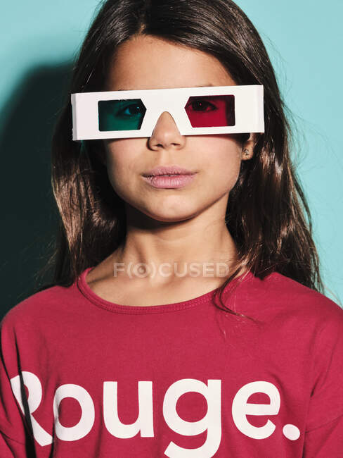 Portrait of happy preteen girl in white plastic stereoscopic glasses with red and blue lens smiling at camera while watching 3d graphic film with pleasure against turquoise background in modern studio — Stock Photo