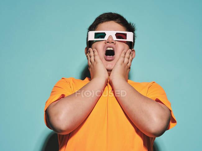 Зачарований здивований підліток з ротом відкритий у спеціальних окулярах з стереоскопічним синім і червоним кришталиком дивлячись геть і насолоджуючись 3d графічним відео проти бірюзового фону в сучасній студії — стокове фото